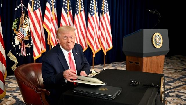 Trump smiles while signing order